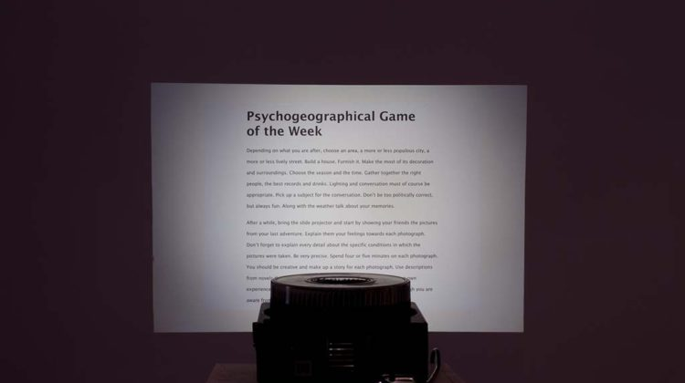 Pedro Barateiro - Psychogeographical Game of the Week - 2007 - Vynil lettering, rotary slide projector, 80 glassless slide mounts, plinth,  Dimensions variable